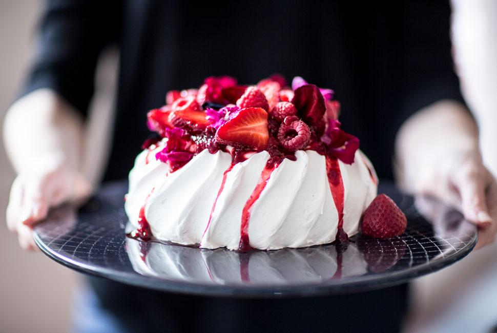 Woman offering a dark blue cake display stand with a Pavlova with berries