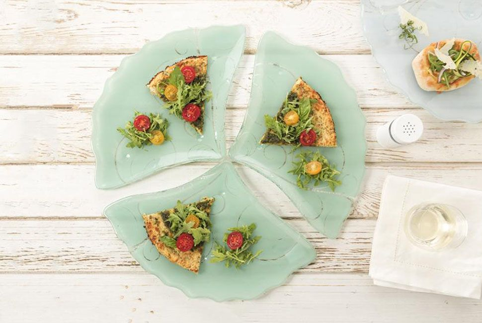 Pizza plate Dora is a lovely fan-shaped tapas plate in jade green with our alluring Vivace pattern. Dora is presenting lovely pizza with cauliflower crust and cherry tomatoes. Dora is positioned on white wood background.