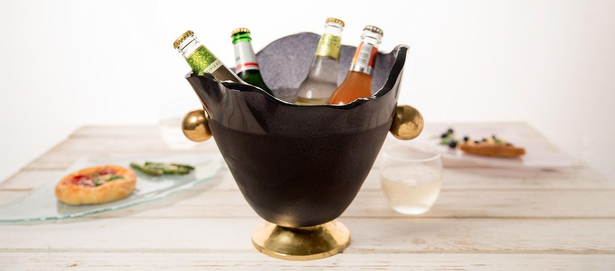 Navy blue champagne bucket with bronze handles and pedestal, with 4 beers and pizza plates in the background.
