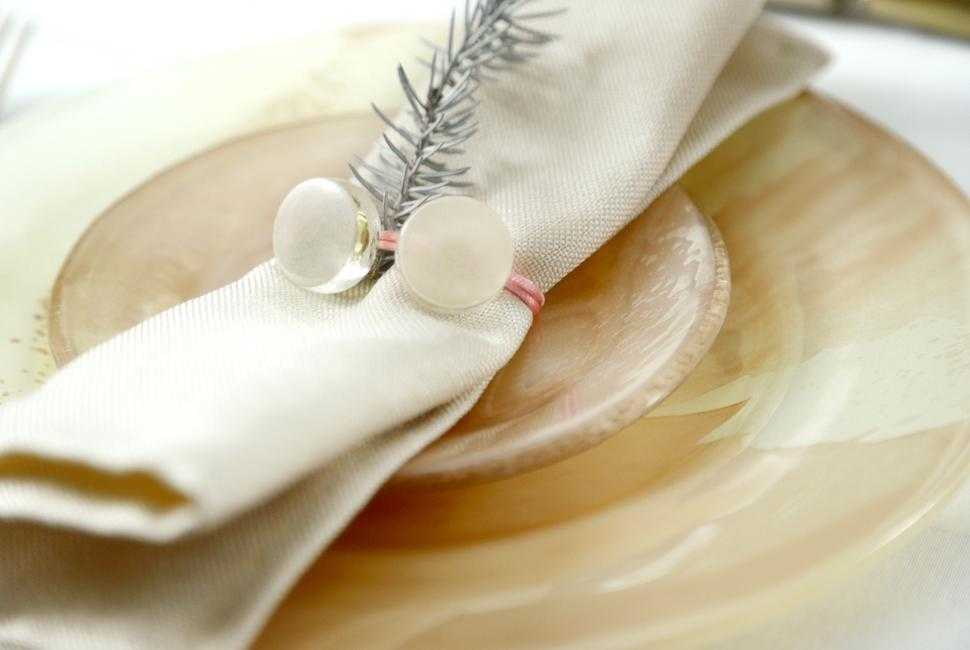 Napkin in a napkin ring with 2 glass gems on top of a coral dinner set.