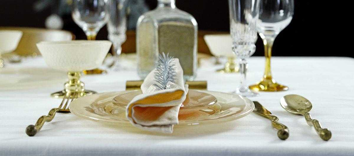 Place setting with a coral dinner set and quirky gold cutlery for a Christmas table.