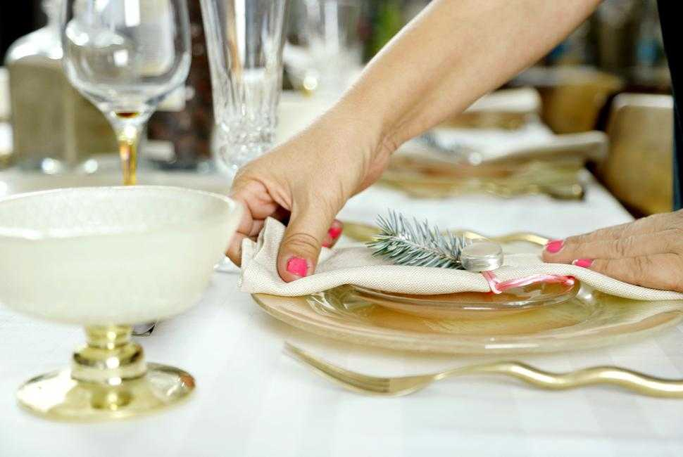 Woman's hands putting a napkin on a plate from a coral dinner set on a table decorated for Christmas with gold cutlery
