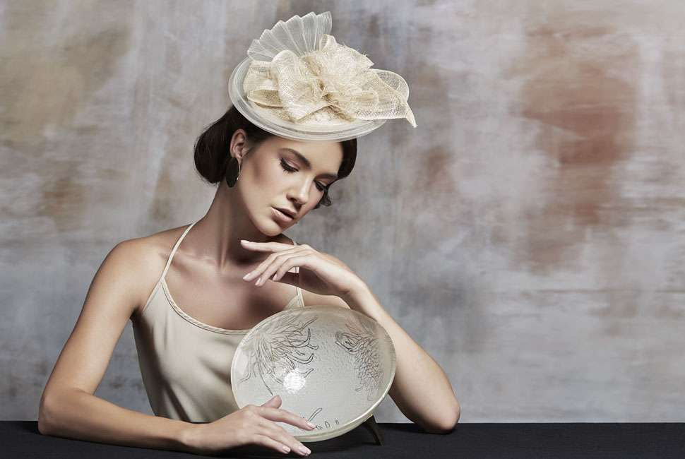 Model dressed in the Melbourne Cup fashion posing with a white glass bowl with bronze feet.