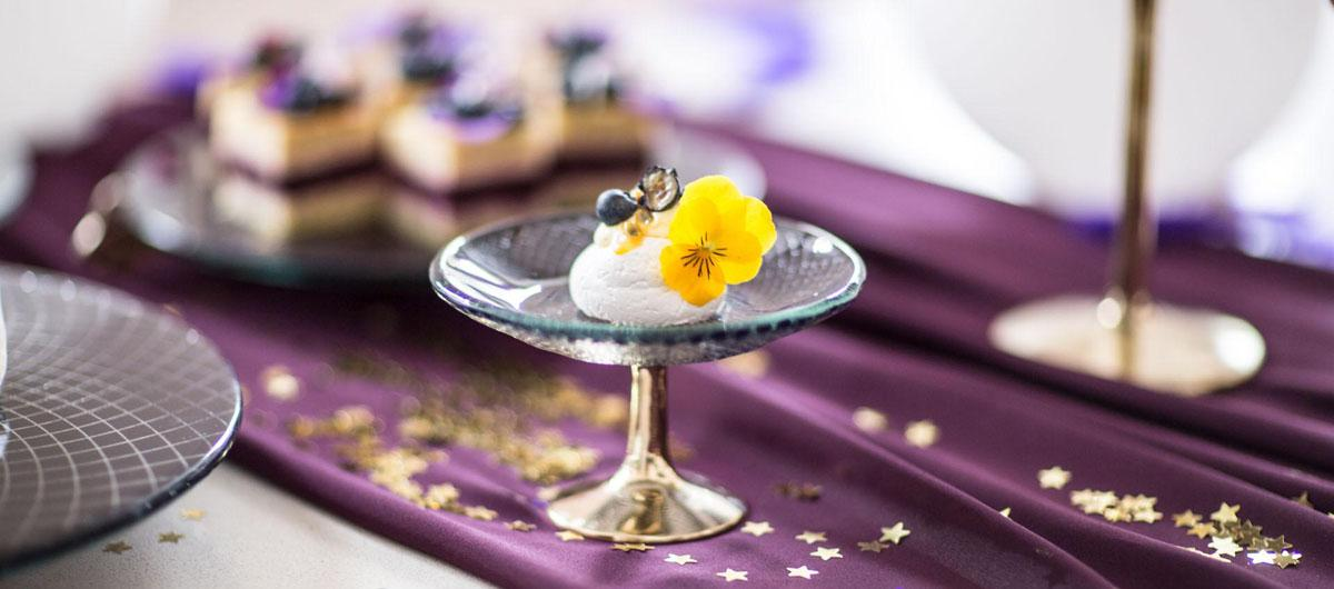 Small navy blue glass cake stand with a bronze pedestal with a petit four decorated with a yellow pansy on a red table runner.