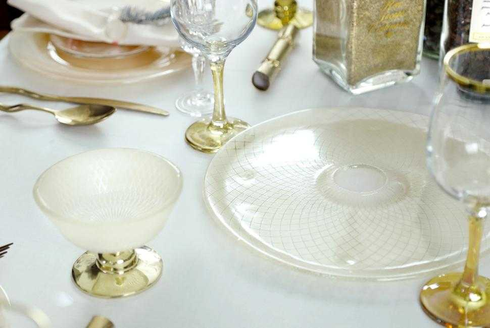 Beige sushi platter from a coral dinner set on an elegant white tablecloth wih gold wine glasses and a beige trifle bowl with a bronze pedestal.
