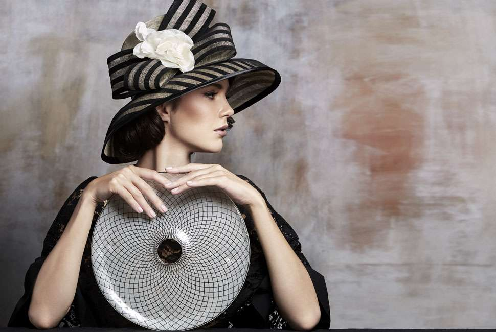 Model dressed in the style of Melbourne Cup holding a round plate with an elegant plate design.