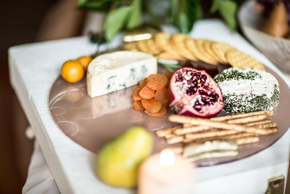 Pink glass cheese platter with cheeses and fruit.