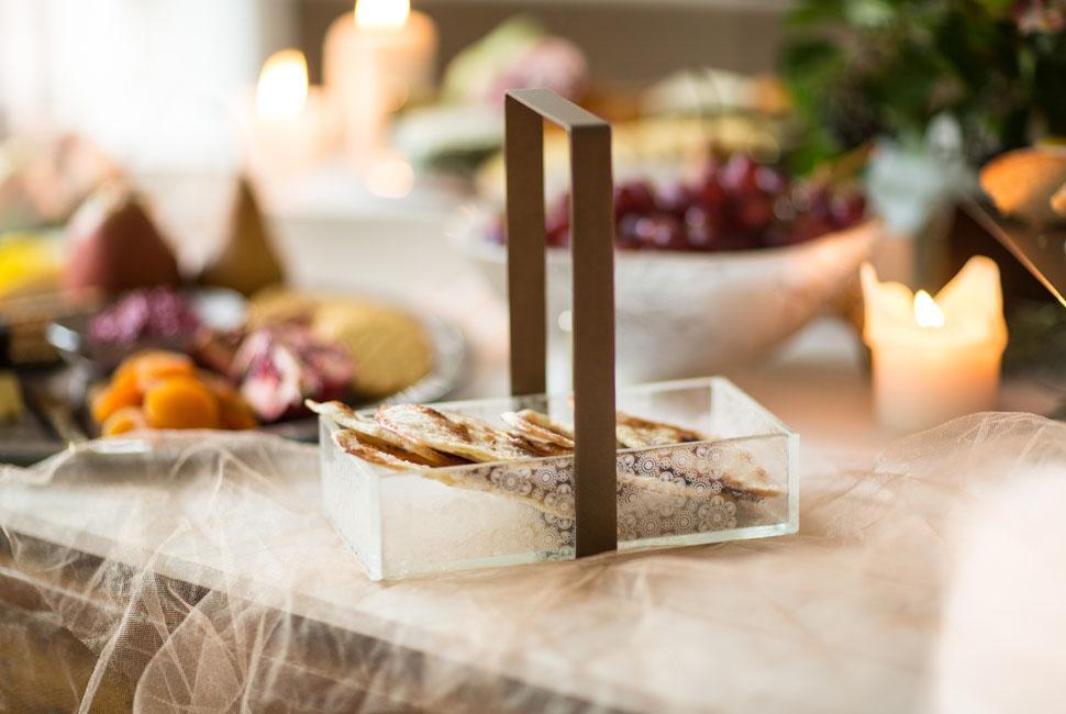Beige glass bread basket with a metal brown loop handle with crackers .