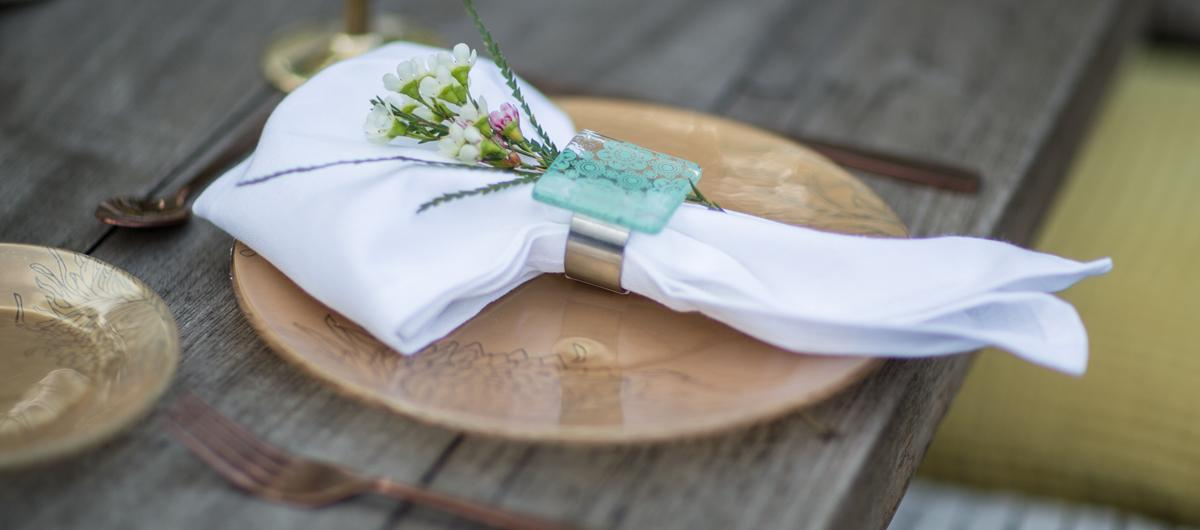Table setting for Australia day with a gold charger plate and a white napkin in a green napkin ring holder.
