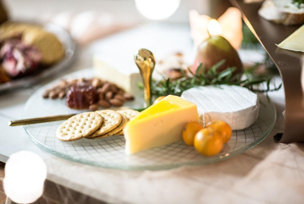 The Diana glass cheese platter with a bronze handle and different cheeses with crackers.