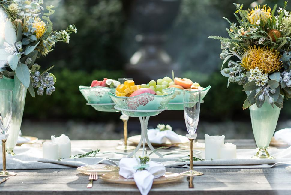 Green gold garden table setting for Australia Day with a green fruit bowl stand with a variety of cut up fruits.