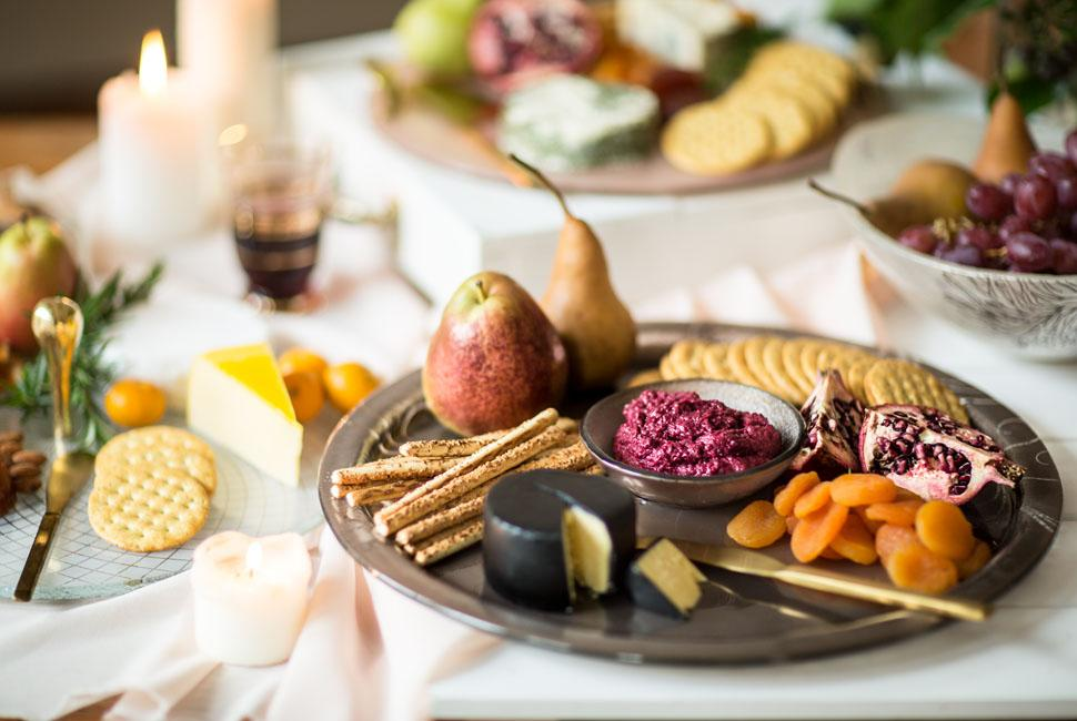 Round glass cheese platter with different cheeses, fruits and crackers for Cheese Day.