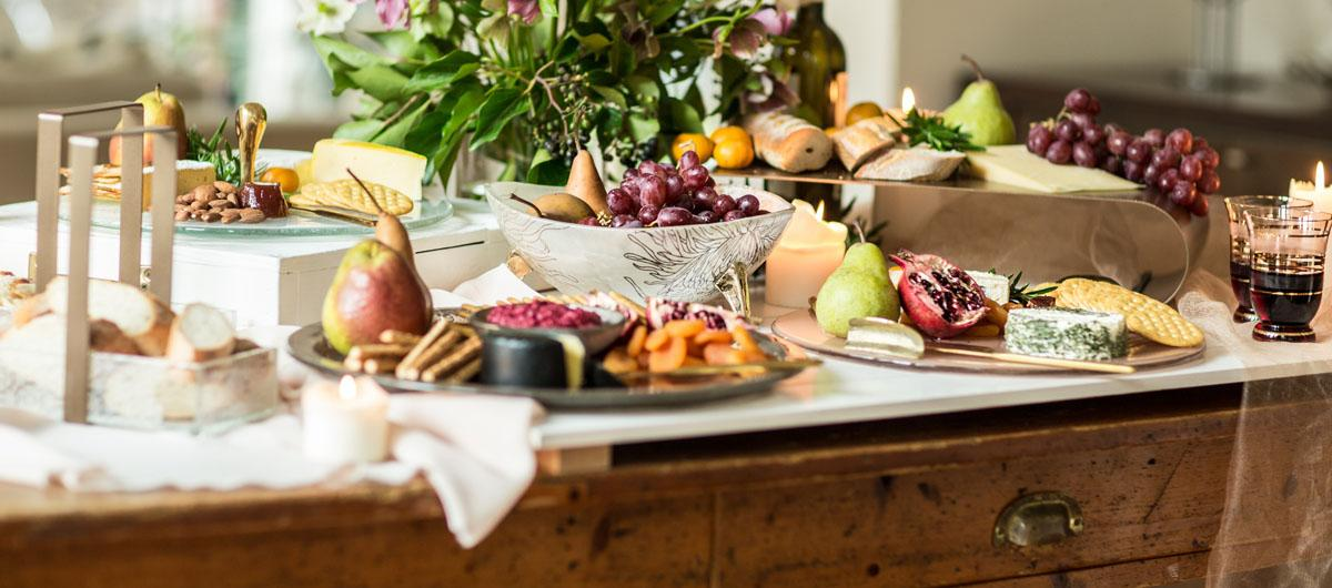 Beautiful table with fruits, cheese and crackers on elegant glass cheese platters and glass cheese trays.
