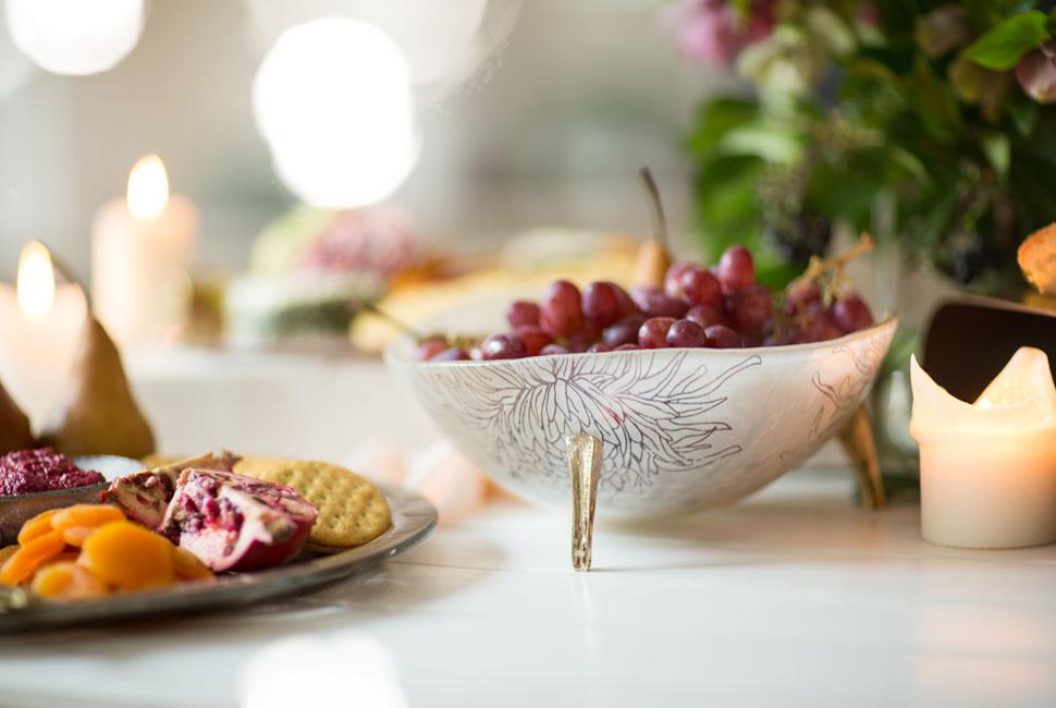 Decorative glass bowl Marc with fruits next to glass cheese platters with cheeses.