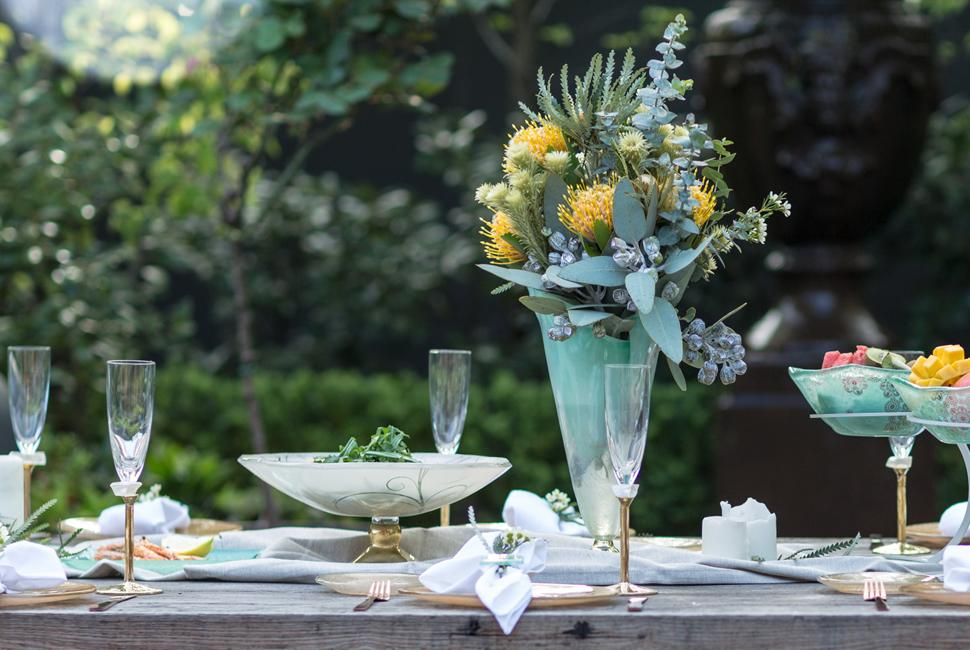 Table setting for Australia Day in a garden with elegant mint green dinnerware and a tall mint green vase with flowers.