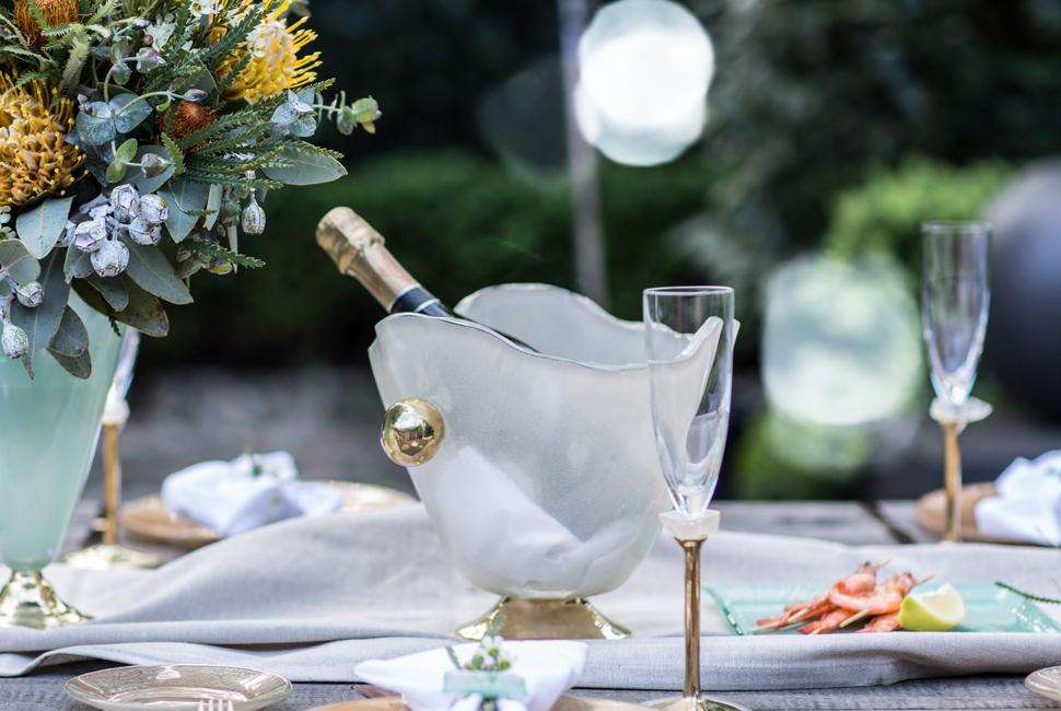 A garden party tablescape with a beige champagne ice bucket with a champagne bottle.