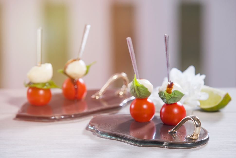 Unique small canape serving platters in the shape of a leaf with a bronze handles with cherry tomatoes appetisers.