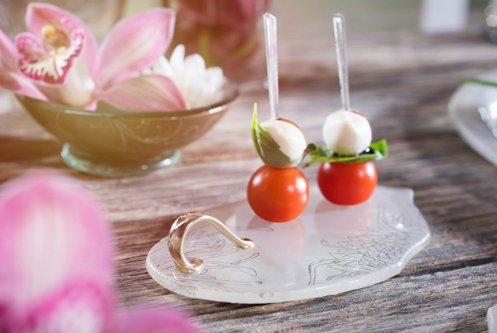 The lovely Elena is a petite canape dish in gentle cream colour patterned with our Perky Chrysanthemum design, with a small shiny bronze handle and is presenting small mozarella and cherry tomatoes bites as part of a Portsea Polo themed table setting
