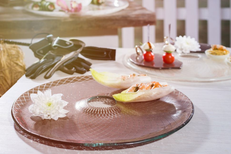 Round brown glass serving platter with an insert in the middle with appetisers and a flower for Portsea Polo.
