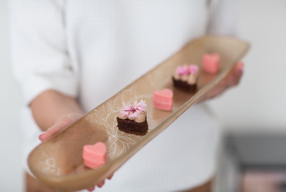 Woman's hands holding matte gold serving platter with small heartshaped desserts in it