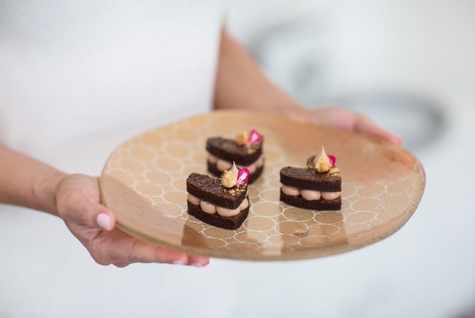 Woman's hands holding wavy gold dinner plate with small heartshaped dessert in it