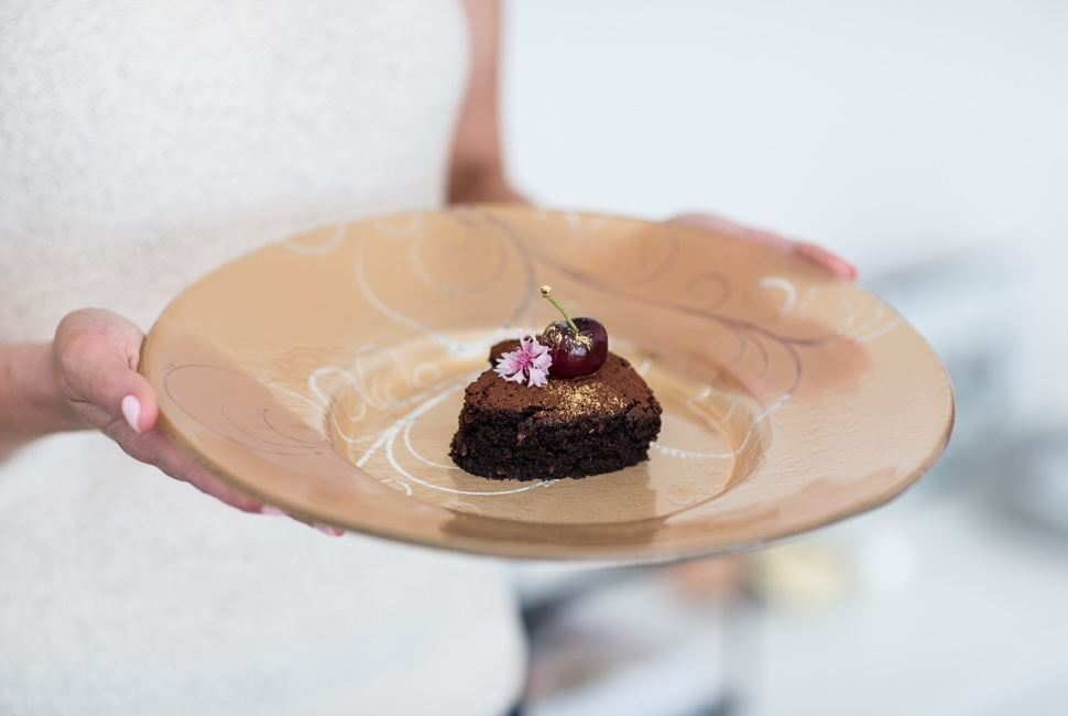Woman's hands holding large floral gold cake plates with small heartshaped dessert on it