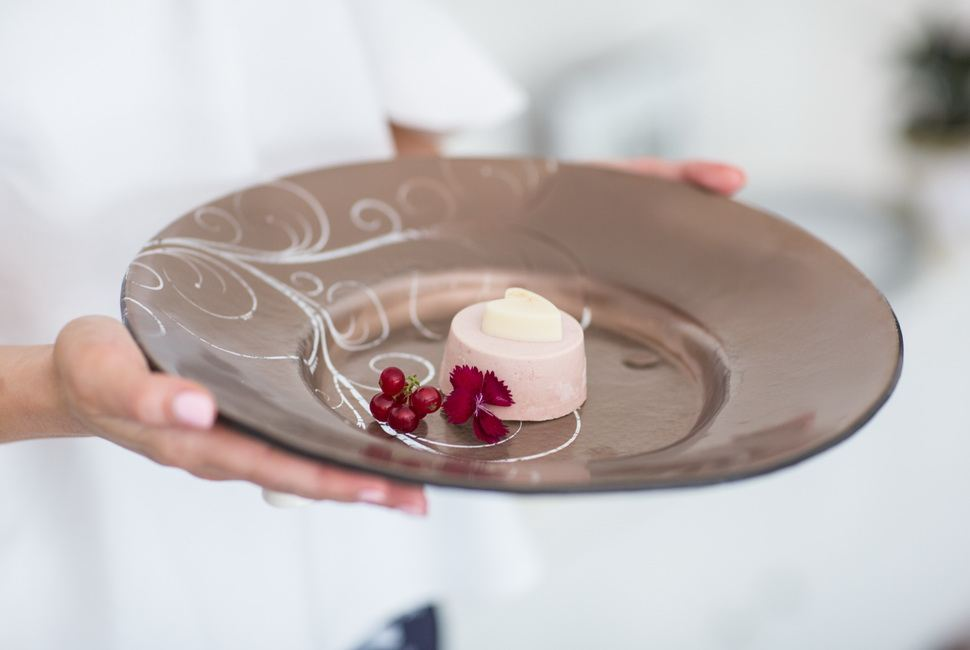 Woman's hands holding large brown valentine plate with small heartshaped dessert in it