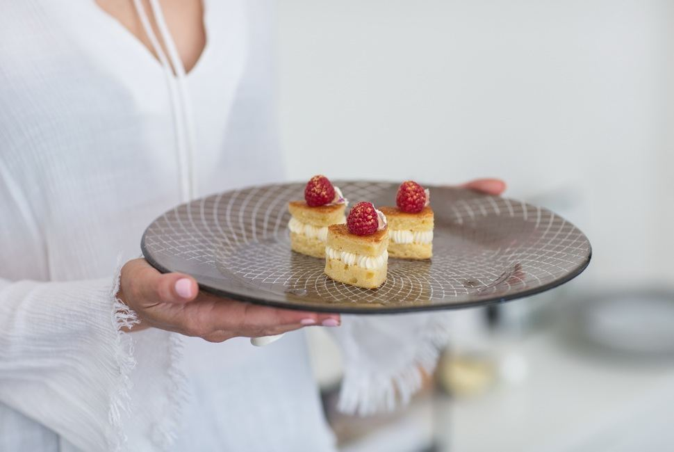 Woman's hands holding large brown cake plates with small heartshaped dessert in it