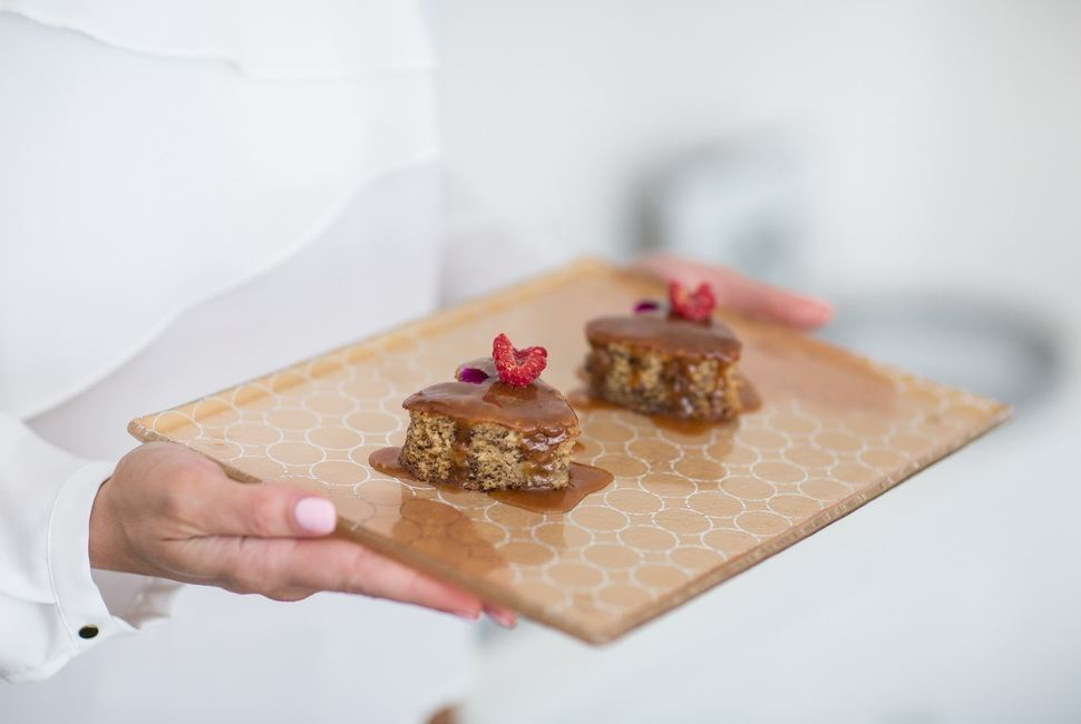 Woman's hands holding Matte gold cheese platter with small heartshaped desserts in it