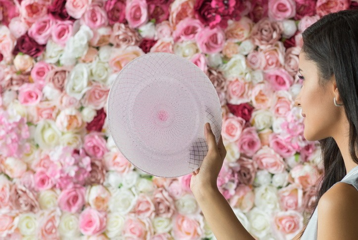 A woman looking into a pink charger plate as if it is a mirror
