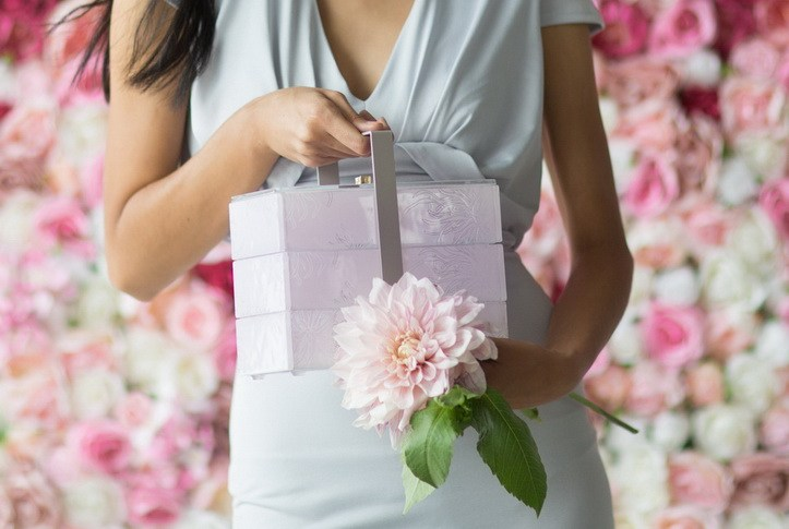 A woman's hands holding a pink bento box from AnnaVasily's pink dinnerware collection and a flower