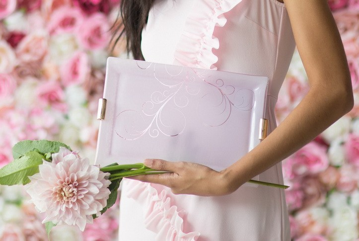 A women holding a pink charger plate with bronze handles, as if she is holding a clutch