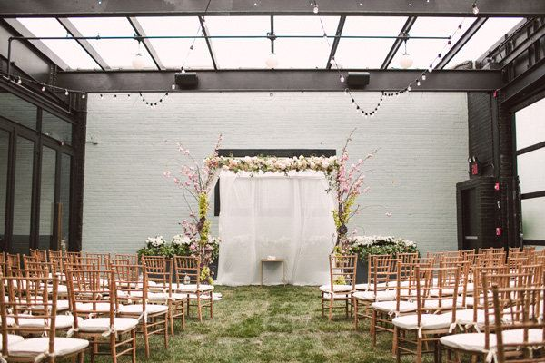 Wedding ideas - indoor wedding setting, wooden chairs, fake grass, glass rooftop