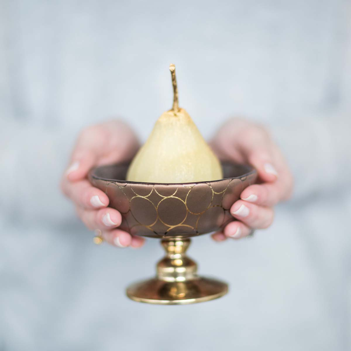 woman's hands holding a retro pattern brown trifle bowl with pedestal and pear