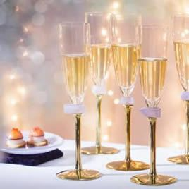Designer tableware brand AnnaVasily's Kassi gold champagne glass set with a brass stem and glass gem with a twinkling background.