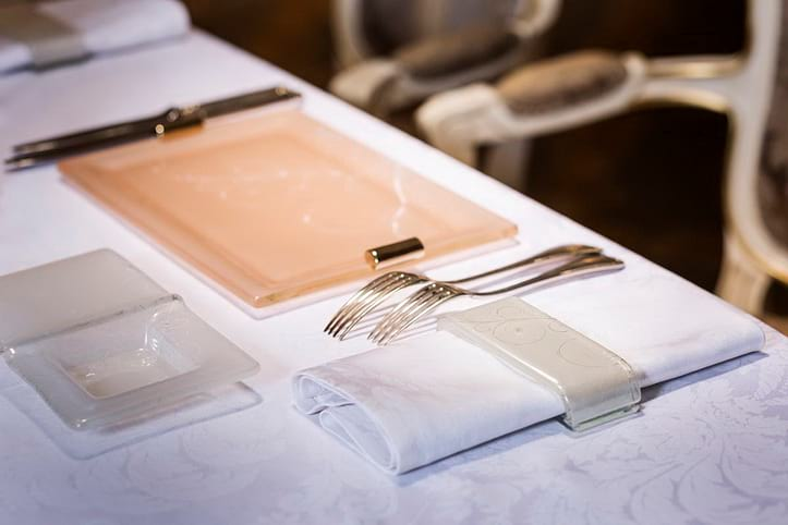 Elegant dinner sets from glass by AnnaVasily on a table with a white tablecloth and napkin with a napkin ring