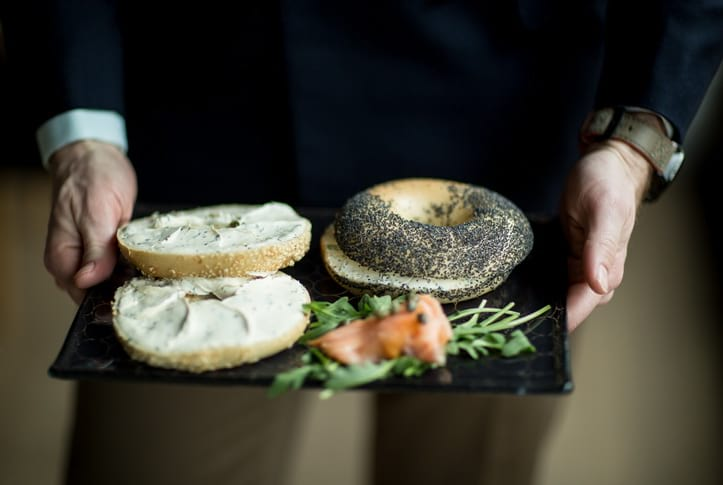 Father's Day table setting with navy blue sushi tray Ivory with a geometric pattern with cream cheese bagels offered by Steve Tilly in a suit.