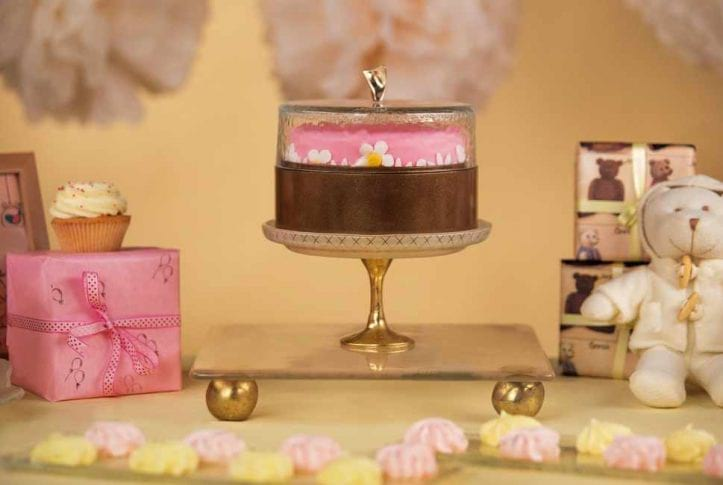 Candy Buffet Ideas WithBeige Cake Serving Board with Pattern and Bronze Supports by Anna Vasily with a Covered Cake Stand and Cake.