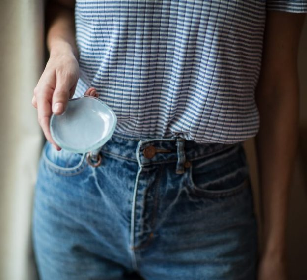 Organic mini dessert dish, Cass set of 6 light blue mini plates by Anna Vasily offered by a woman.