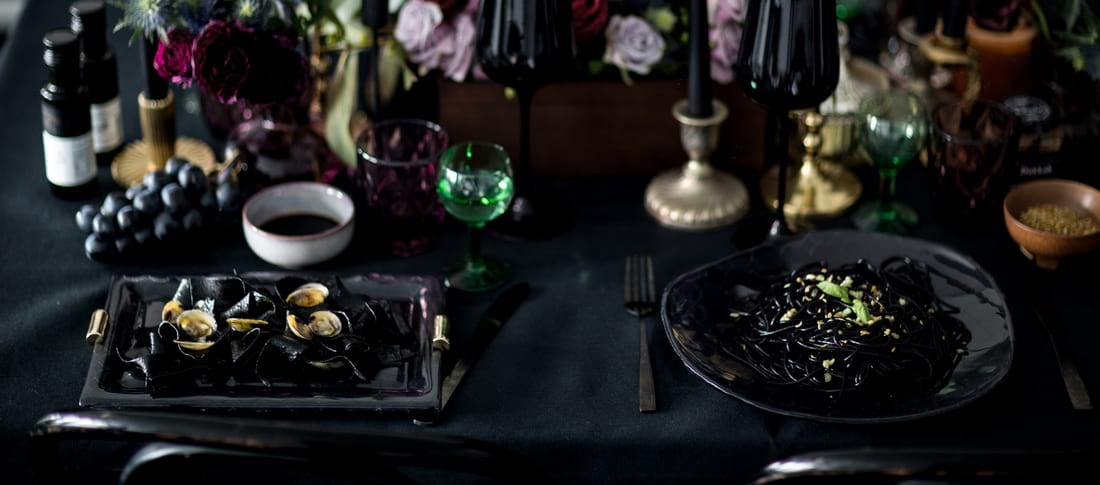 Halloween Dinner Party tablescapes - place setting with black plates with squid ink pasta.