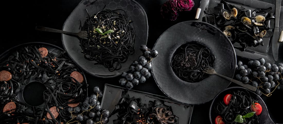 Halloween dinner party table setting with blue black plates and platters with squid ink pasta. Bewitching Halloween tablescapes!