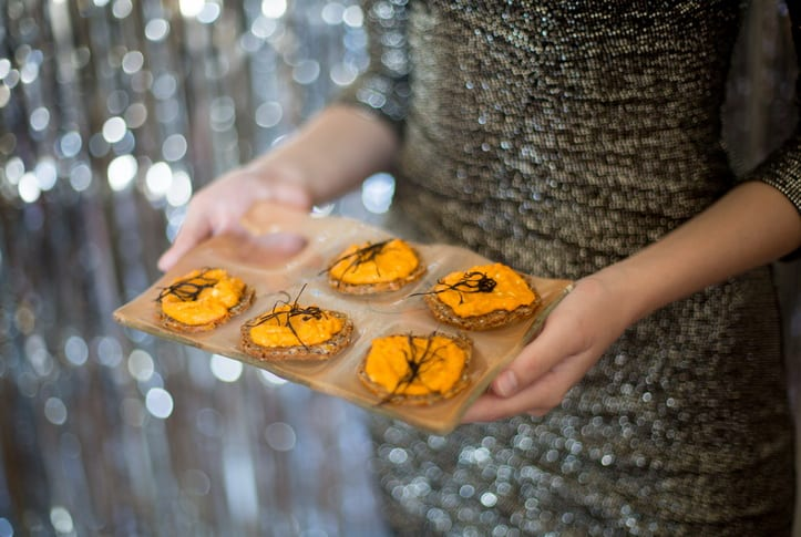 Gold wine plates that hold a glass with canapes for a glam NYE party.