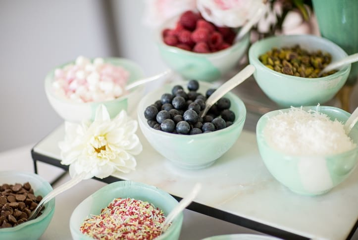 Mint green bowls for toppings at a Mother's Day party's waffle bar.