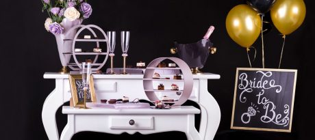 Unique partyware for a Bachelorette party with round high tea stands, champagne glasses and a champagane bucket on a white table with a black background.
