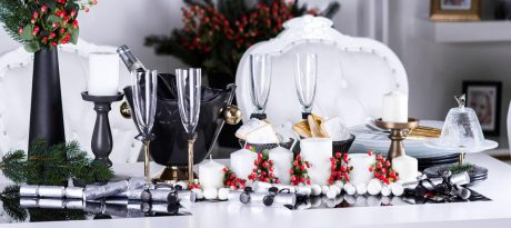 Christmas in July navy blue table setting with navy blue dinnerware and gold champagne glasses with white linen and pearls and Christmas decoration.