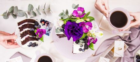 Top view of table with designer pink tea cups, coffee cake desserts on a glass plate by AnnaVasily and flowers.