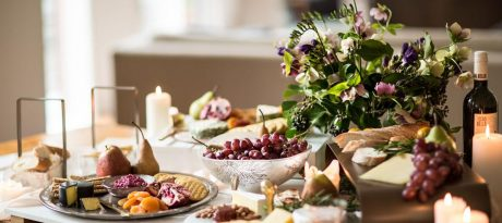 Beautiful table with fruits, cheese and crackers on glass cheese platters and cheese trays.