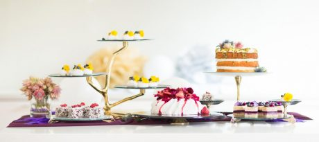 Different luxurious glass cake stands and cake display stands with bronze pedestals with cakes, a Pavlova, lamingtons and petit fours.