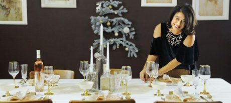 AnnaVasily's tableware designer Anna setting the table for Christmas with a coral dinner set.