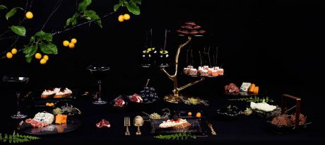 Dark and mysterious Halloween tablescape with a dark blue 3 tiered high tea stand on a bronze tree, twin bowls with chocolate, square plates with floral pattern with appetizers, fruit bowl with fruits inside and finger food platter in Filigree pattern.